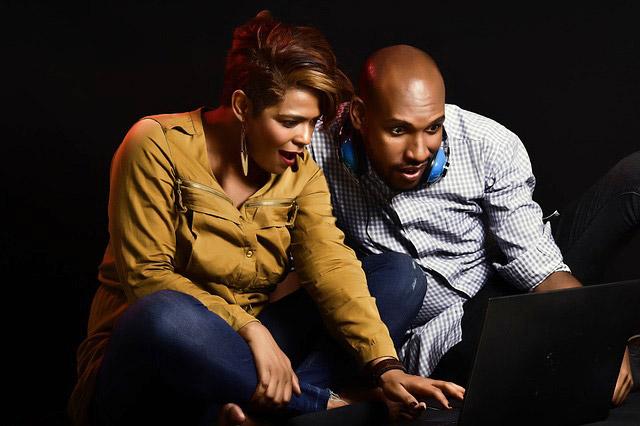 パソコンの画面を見て驚くカップル