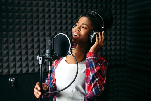 ヘッドホンに手をあてて歌う女性
